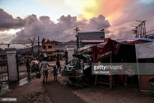 People take shelter under plastic sheets next to the wreck of a bus known locally as a Jeepney outside the Tacloban astrodome evactuatuion centre on...