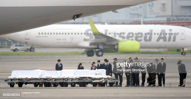 People take the moment of silence as the coffins of seven Japanese victims in the Dhaka terrorist attack arrive back on the special Japanese...