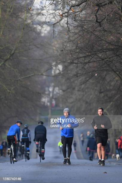 People take their daily excercise in Greenwich Park, south east London on January 23 during the novel coronavirus COVID-19 pandemic. - England has...