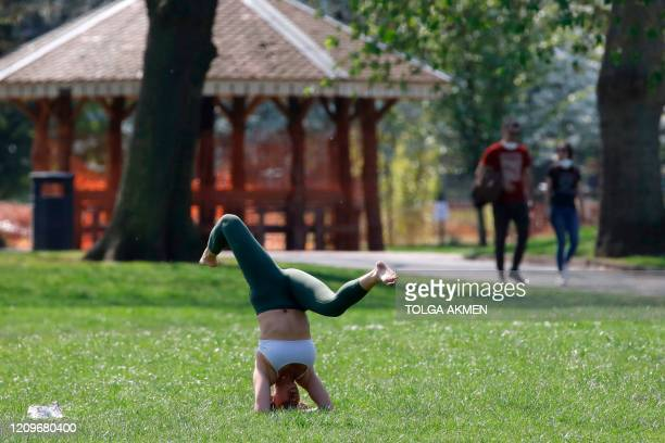 People take their daily excercise in Victoria Park, east London on April 11, 2020 as warm weather tests the nationwide lockdown due to the novel...
