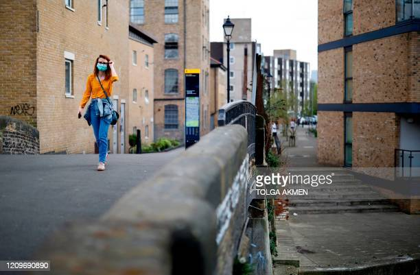 People take their daily excercise on the towpath alongside the Hertford Union Canal in east London on April 11 2020 as warm weather tests the...