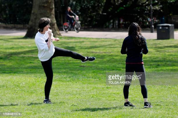 People take their daily exercise allowance in Battersea Park in London on March 28 as life in Britain continues during the nationwide lockdown to...