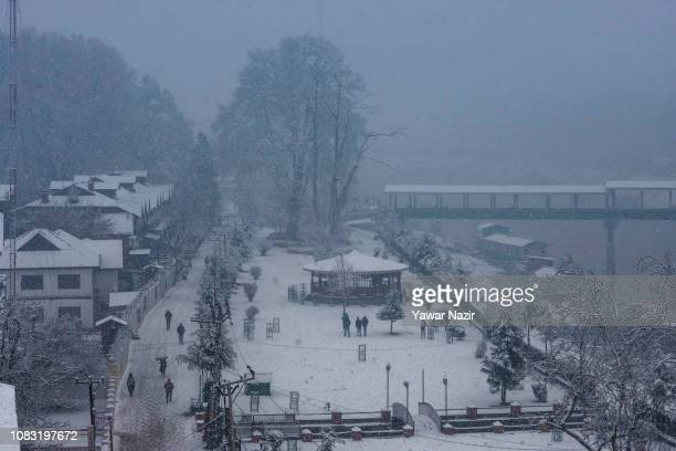 People take their photos in a snow covered park during a fresh snowfall on January 16 2019 in Srinagar the summer capital of Indian administered...