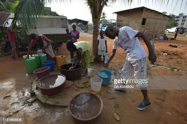 People take water from a well in the popular district of Yopougon where inhabitants lack of of drinking water in Abidjan on March 21 2019 a day...