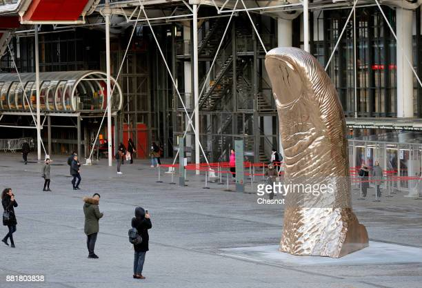 People takes a picture of a giant bronze thumb sculpture by French artist Cesar Baldaccini known as Cesar displayed outside the Centre Pompidou...