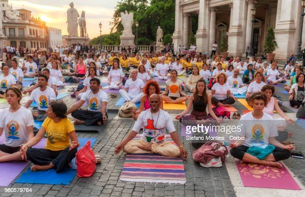 People takes part in a mass yoga session to celebrate the summer solstice and mark International Yoga Day at Campidoglio square in Rome on June 21...