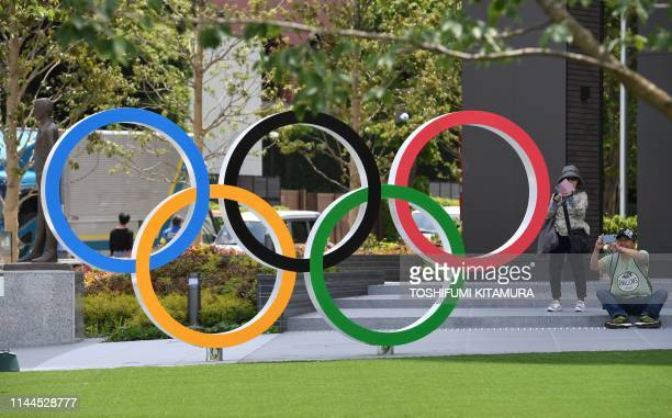 People takes photographs of the Olympic Ring at the Japan Sport Olympic Square beside the under constructing national stadium in Tokyo on May 18,...