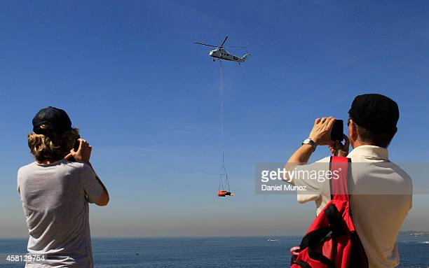 People takes pictures to a van that flies over Bondi Beach to celebrate the start of Movember at Bondi Beach on October 31 2014 in Sydney Australia...