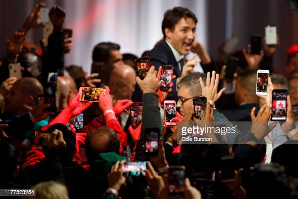 People takes pictures with their phones as Liberal Leader and Canadian Prime Minister Justin Trudeau appears to deliver his victory speech at his...