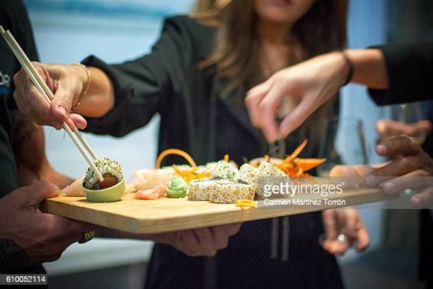 people taking a piece of sushi of a tray. - sushi restaurant stock photos and pictures