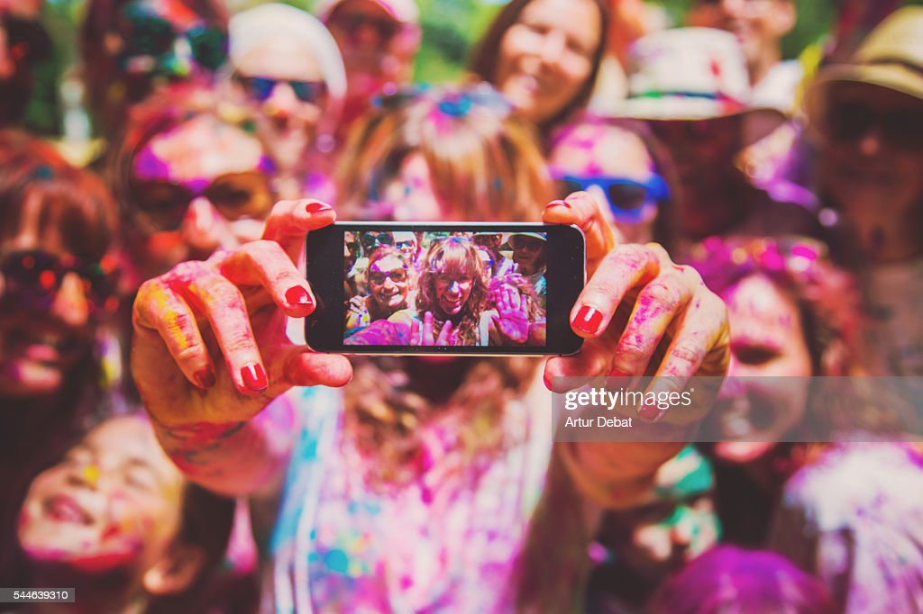 People taking a selfie together in group during a Holi celebration party in the outdoor with happiness expressions and covered with vivid colors. : Stock Photo