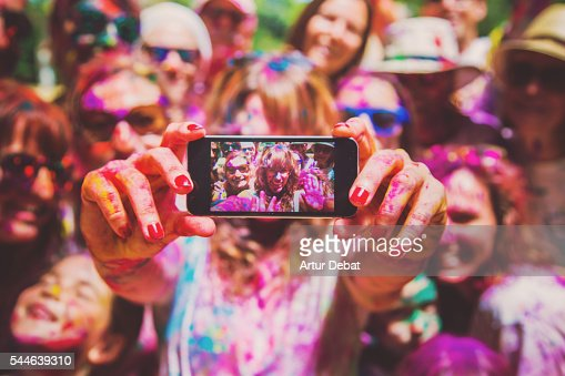 People taking a selfie together in group during a Holi celebration party in the outdoor with happiness expressions and covered with vivid colors.
