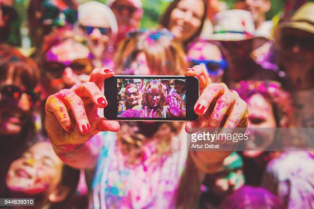 people taking a selfie together in group during a holi celebration party in the outdoor with happiness expressions and covered with vivid colors. - feriado evento - fotografias e filmes do acervo