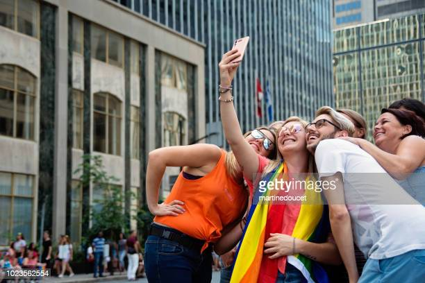 "people taking a selfie waiting for the lgbtq pride parade in montreal street. - ""martine doucet"" or martinedoucet stock pictures, royalty-free photos & images"