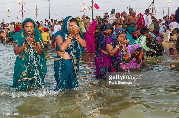 People taking bath early morning at the Sangam the confluence of the rivers Ganges Yamuna and Saraswati at Kumbha Mela