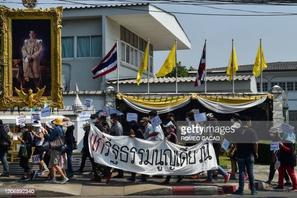 People taking part in a demonstration calling for the creation of a new constitution walk past a portrait of Thailand's King Maha Vajiralongkorn in...