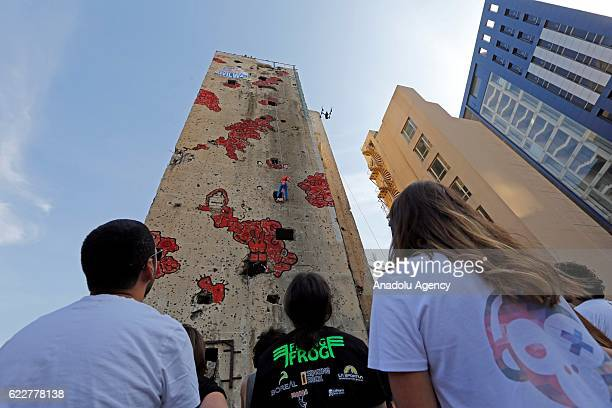 People taking part in the competition, held in the Bishara El Huri region of the capital Beirut, try to climb the entire wall using holes created in...