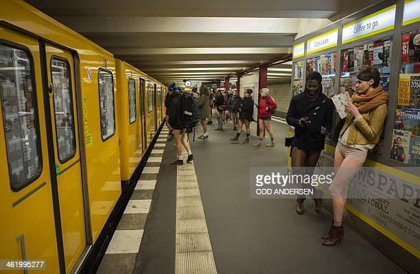 People taking part in the No Pants Subway Ride stand next to a newspaper booth on the platform at the Potsdamer Platz station on the U2 Subway line...
