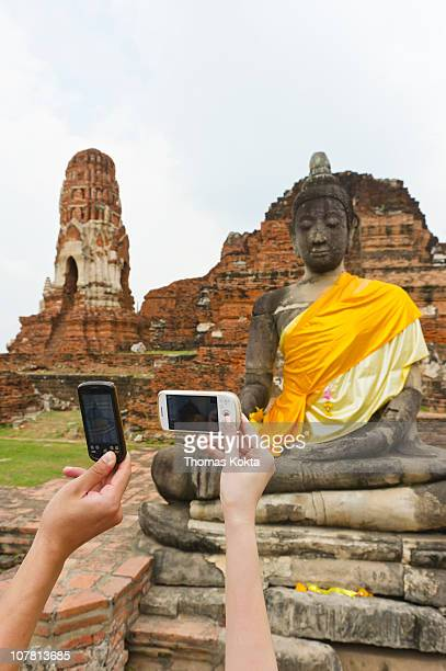 People taking photos of statue with their phones