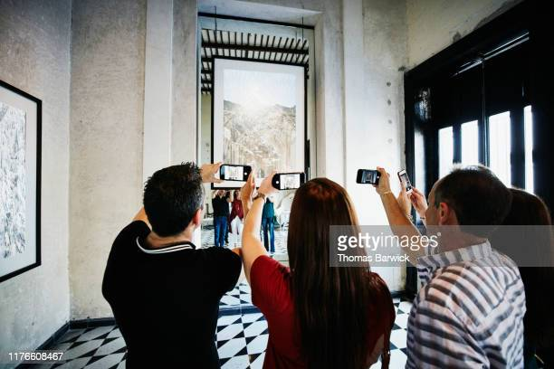 people taking photos with smart phones of artwork while touring museum - photo messaging stock pictures, royalty-free photos & images