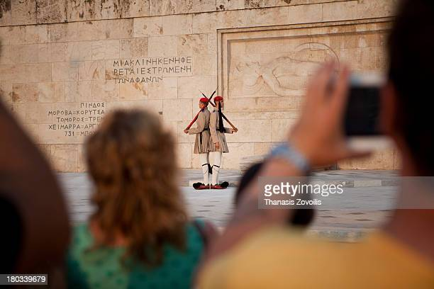 People taking pictures of Greek Evzones in summer service uniform changing guards at the tomb of the unknown soldier on 10 August 2013 in Athens,...