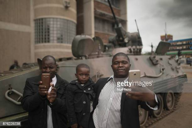 People taking pictures with one of the armored vehicles in the streets of the capital Harare Zimbabwe on 19 November 2017 a day after huge crowds...