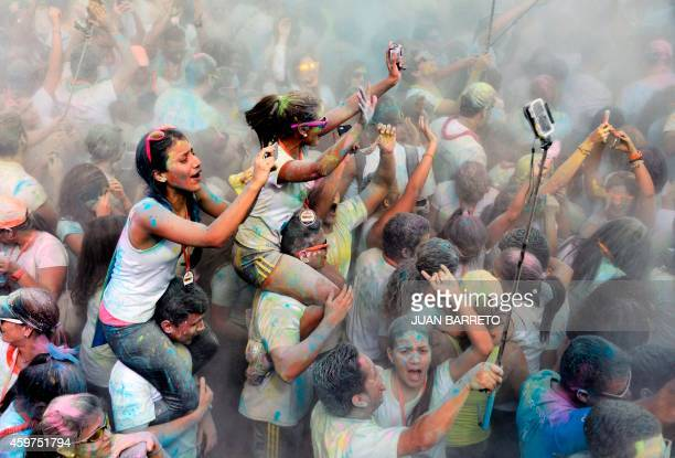 People taking selfies get covered by color powder as they take part in the Color Run also known as the 'Happiest 5K on the Planet' in Caracas on...
