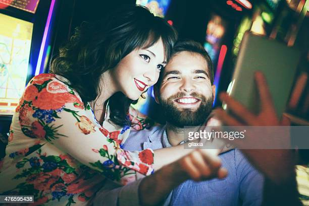 People taking selfies in casino.