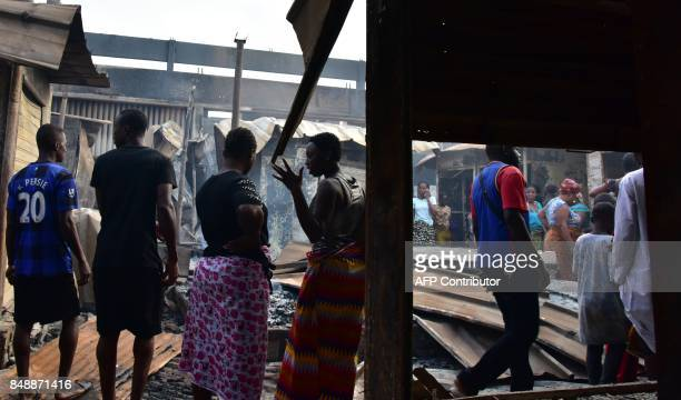 People talk amid debris in the market after a fire devastated the building during the night on September 18 2017 in Abobo neighborhood of Abidjan /...