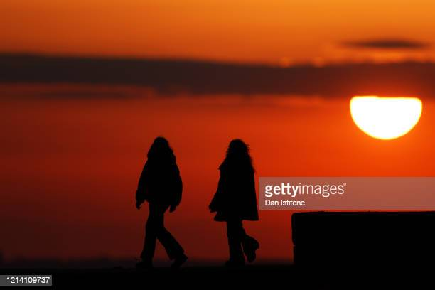 People talk as they take a walk along the seafront after recent incidents of members of the public ignoring government advice on social distancing on...