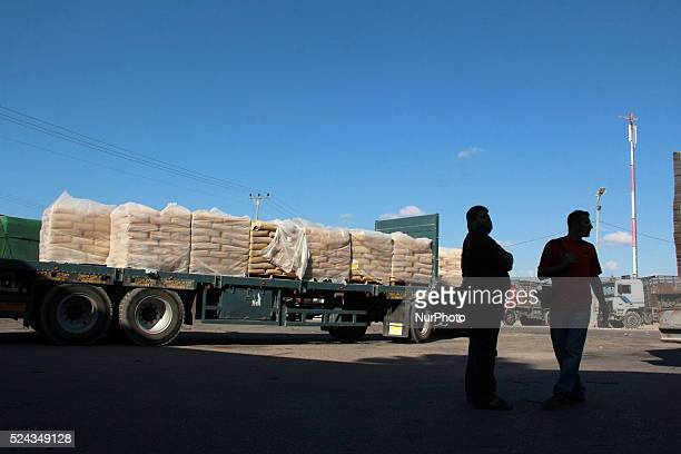 People talk in front of a truck loaded with bags of cement entering the Gaza Strip from Israel through the Kerem Shalom crossing on October 14 in...
