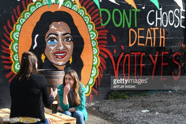 People talk over a drink in front of a prochoice mural urging a yes vote in the referendum to repeal the eighth amendment of the Irish constitution a...