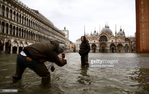 """People talk photos in the middle of a flooded St. Mark's Square on December 8, 2020 in Venice following a high tide """"Alta Acqua"""" event following..."""