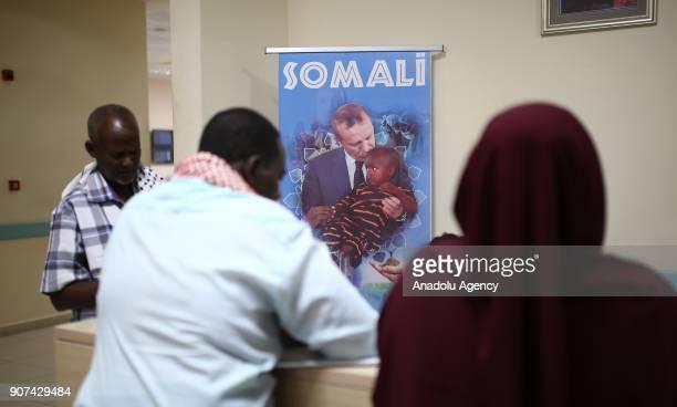 People talk to information desk staff as a portrait of Turkish President Recep Tayyip Erdogan is seen on a wall of Recep Tayyip Erdogan Training...