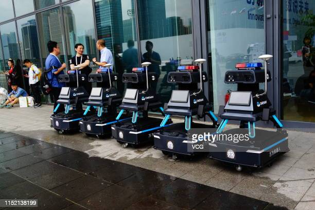 People talk with each other next to Oneway security robots on the opening day of China International Big Data Industry Expo 2019 at Guiyang...