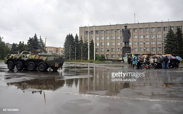 People talk with Ukrainian officials as a Ukrainian APC guards the city hall of Slavyansk on July 7, 2014. Retreating pro-Russian insurgents dug in...