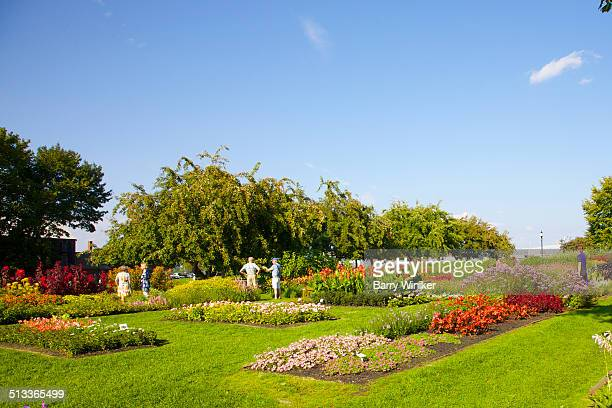 People talking amid colorful garden beds