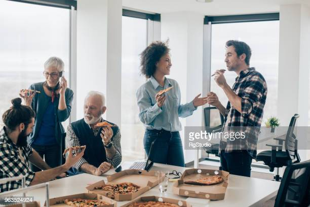 people talking and having pizza on lunch break at office - senior lunch stock photos and pictures