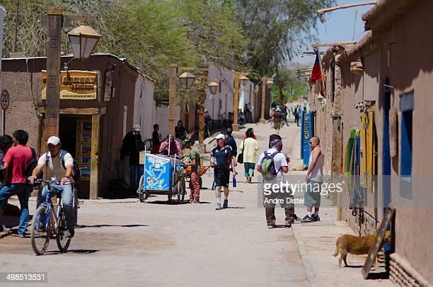 People talking and riding their bikes on the unpaved streets of San Pedro de Atacama in the Atacama Desert.
