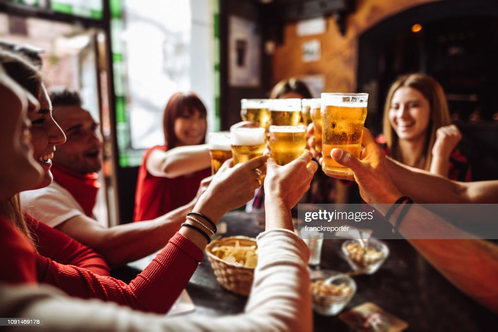 people talking and toasting in a pub with the beers : Stock Photo