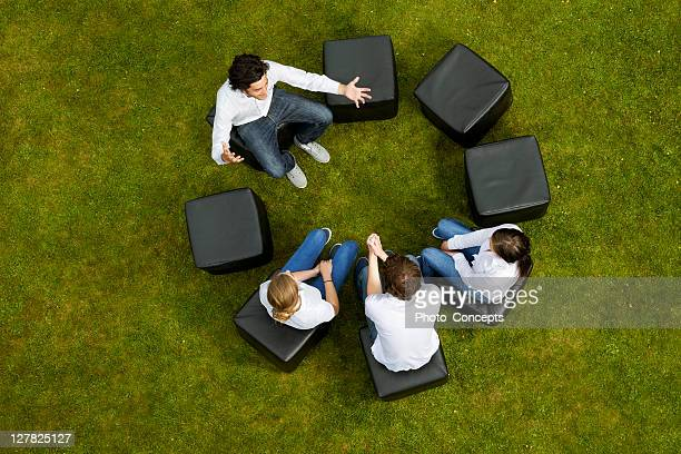 people talking in circle in grass - group of objects stock pictures, royalty-free photos & images