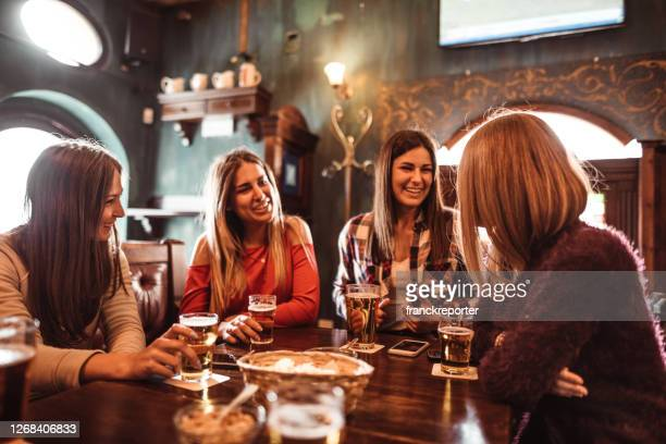 people talking indoors in a pub with the beers - girlfriend stock pictures, royalty-free photos & images