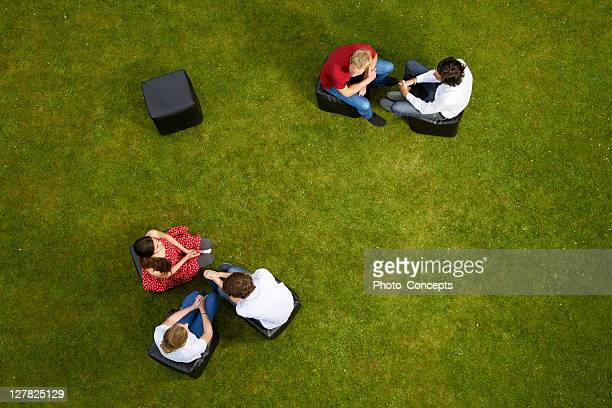 People talking on chairs in grass