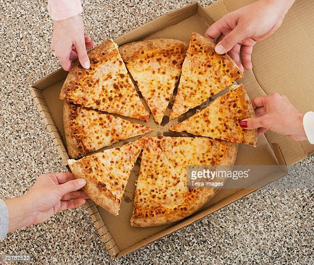 People talking slices of pizza from box