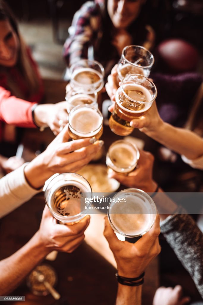 people talking toasting in a pub with the beers : Stock Photo