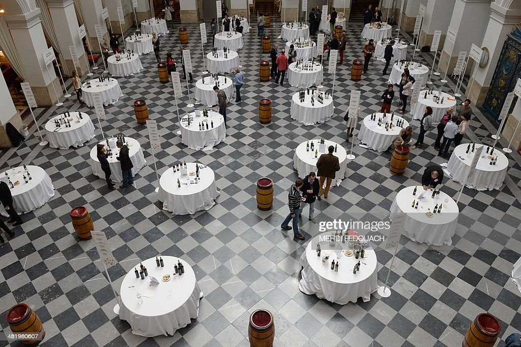 People taste 2013 vintage wines at the Palais de la Bourse in Bordeaux, south-eastern France, on April 2, 2014, as around 50 wine producers from the Graves region of Bordeaux present their 2013 red and white vintage wines. The primeur campaign attracts some 6,000 professionals from the wine sector to taste and order the 2013 wine production at better prices before they go on sale two years later.