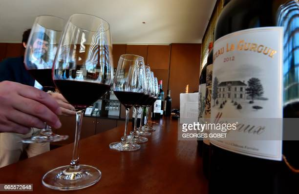 People taste wine during a tasting of the 2016 vintage Bordeaux primeurs at Chateau Ferriere in Margaux on April 4 2017 Professionals from all over...