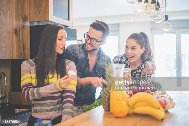 People tasting food in the kitchen