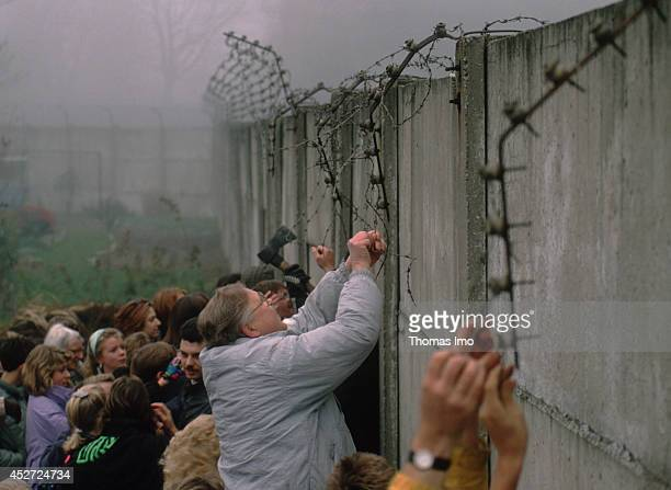 People tearing down barb wire from the Berlin Wall after opening of the border on November 09 in Berlin, Germany. The year 2014 marks the 25th...