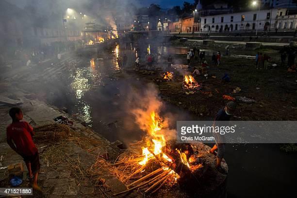 People tend to the cremation of an earthquake victim at Pashupatinah Temple on April 29 2015 in Kathmandu Nepal A major 78 earthquake hit Kathmandu...